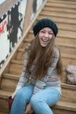 Belle fille s'asseyant sur les escaliers en bois Images stock