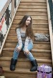 Belle fille s'asseyant sur les escaliers en bois Photo stock