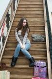 Belle fille s'asseyant sur les escaliers en bois Photographie stock