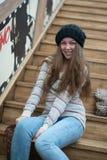 Belle fille s'asseyant sur les escaliers en bois Photo libre de droits
