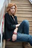 Belle fille s'asseyant sur les escaliers en bois Image stock