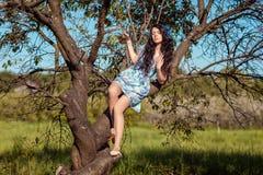 Belle fille s'asseyant sur un arbre Photographie stock libre de droits