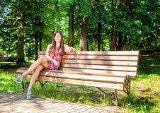 Belle fille s'asseyant sur un banc de parc Photo stock