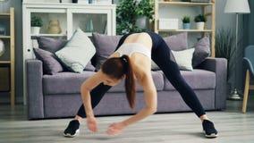 Belle fille s'exerçant à la maison pliant étirer en avant les jambes et le dos banque de vidéos