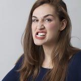 Belle fille 20s fâchée rectifiant ses dents menaçant Photo libre de droits