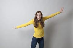 Belle fille 20s étonnée agissant comme un avion Photographie stock