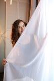 Belle fille se cachant derrière le rideau Images libres de droits