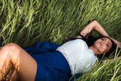 Belle fille se couchant à l'herbe images stock