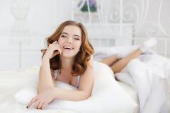 Belle fille se réveillant dans le lit blanc Photo libre de droits