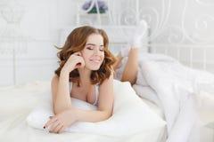 Belle fille se réveillant dans le lit blanc Photographie stock libre de droits