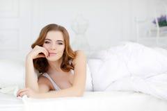 Belle fille se réveillant dans le lit blanc Photos stock