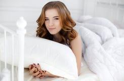 Belle fille se réveillant dans le lit blanc Photo stock