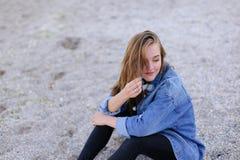 Belle fille se reposant, s'asseyant par la mer et posant sur l'appareil-photo sur b Photo libre de droits