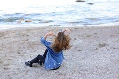 Belle fille se reposant, s'asseyant par la mer et posant sur l'appareil-photo sur b Photo stock