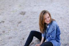 Belle fille se reposant, s'asseyant par la mer et posant sur l'appareil-photo sur b Photos libres de droits