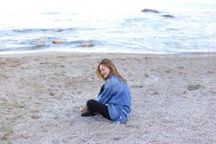 Belle fille se reposant, s'asseyant par la mer et posant sur l'appareil-photo sur b Image libre de droits