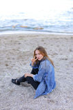 Belle fille se reposant, s'asseyant par la mer et posant sur l'appareil-photo sur b Images libres de droits