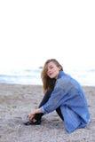Belle fille se reposant, s'asseyant par la mer et posant sur l'appareil-photo sur b Photos stock