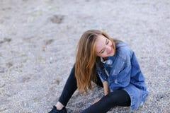 Belle fille se reposant, s'asseyant par la mer et posant sur l'appareil-photo sur b Images stock