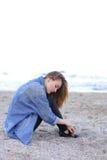 Belle fille se reposant, s'asseyant par la mer et posant sur l'appareil-photo sur b Photographie stock