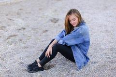 Belle fille se reposant, s'asseyant par la mer et posant sur l'appareil-photo sur b Photographie stock libre de droits