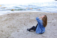 Belle fille se reposant, s'asseyant par la mer et posant sur l'appareil-photo sur b Image stock