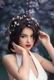 Belle fille se tenant à l'arbre de floraison dans le jardin Images libres de droits