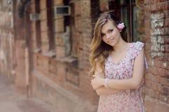 Belle fille se tenant au mur de briques Image libre de droits