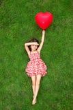 Belle fille se trouvant sur l'herbe et tenant une boule rouge dans Photographie stock