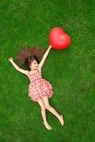 Belle fille se trouvant sur l'herbe et tenant une boule rouge dans Photographie stock libre de droits