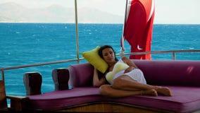 Belle fille se trouvant sur le sofa sur un yacht un jour d'été banque de vidéos