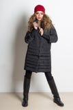 Belle fille sexy avec le maquillage lumineux posant dans le manteau dans le studio sur un fond blanc, tir pour le catalogue Photo libre de droits