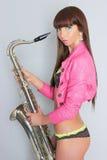 Belle fille sexy avec le saxophone photographie stock