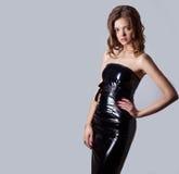 Belle fille sexy dans une robe en cuir noire avec de grandes lèvres et cheveux rouges, studio de photographie Images stock