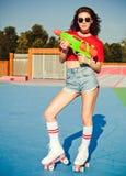 Belle fille sexy de portrait posant sur des patins de rouleau de vintage Derby dans les shorts de denim, le T-shirt blanc et des  Photos stock