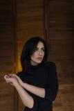Belle fille songeuse dans le chandail noir dans le studio Images stock