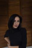 Belle fille songeuse dans le chandail noir dans le studio Photo stock