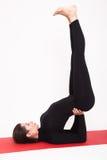 Belle fille sportive dans le costume noir faisant le yoga asana de sarvangasana de salamba - support sur des lames D'isolement Photo stock