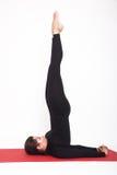 Belle fille sportive dans le costume noir faisant le yoga asana de sarvangasana de salamba - support sur des lames D'isolement, b Photo libre de droits