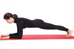 Belle fille sportive dans le costume noir faisant le yoga Pose de planche d'asana de Kumbhasana sur des coudes Fond blanc d'isole Photos libres de droits