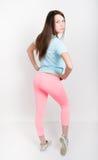 Belle fille sportive mince dans des guêtres roses, un dessus de réservoir bleu et des espadrilles colorées Photographie stock libre de droits