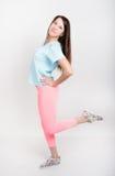 Belle fille sportive mince dans des guêtres roses, un dessus de réservoir bleu et des espadrilles colorées Photographie stock