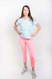 Belle fille sportive mince dans des guêtres roses, un dessus de réservoir bleu et des espadrilles colorées Photos stock