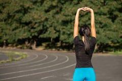 Belle fille sportive s'étirant avant le fonctionnement au stade Tir extérieur avec des rayons du soleil L'espace vide photo libre de droits