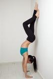 Belle fille sportive se tenant sur des mains près du mur blanc Photographie stock
