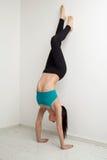 Belle fille sportive se tenant sur des mains près du mur blanc Image stock