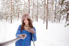Belle fille sur des skis dans les bois faisant un selfie Images libres de droits