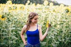 Belle fille sur le champ avec des tournesols dans des shorts courts et un gilet image stock