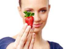Belle fille sur le fond blanc tenant une fraise Photographie stock libre de droits