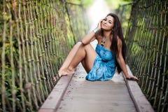 Belle fille sur le pont en bois suspendu Photos stock